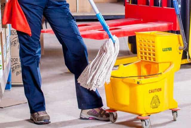Mop and yellow mop bucket beside employee